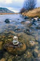 staplade stenar i floden. foto