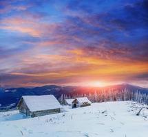 stuga i snöiga berg med fantastiska vinterträd foto