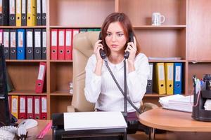 besviken kvinna med två telefoner foto