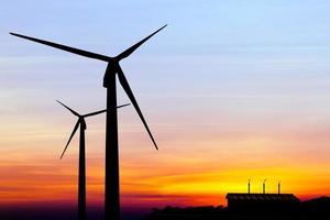 silhuett vindkraftverk med fabriksutsläpp av kolhydrater foto