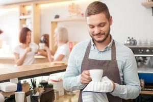 attraktiv manlig arbetare betjänar kunder i cafeterian foto