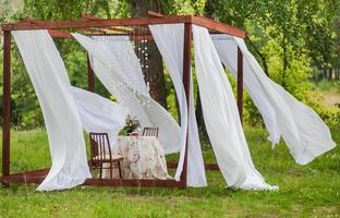 utomhusgazebo med vita gardiner. bröllop dekorationer. konst objekt foto