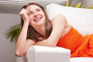 skratt av en ung kvinna på en soffa foto