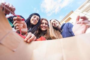 glada kvinnor som tittar in i shoppingväskan foto