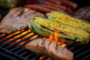 korv, biffar och lax på en grill