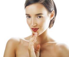ung brunett kvinna med händerna på ansiktet isolerad vit bakgrund foto