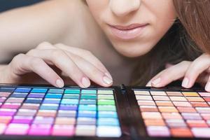 vacker kvinna med färgglad palett för modesmink foto