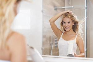 naturlig kvinna framför spegeln som torkar hår foto