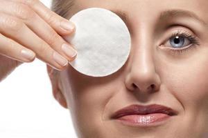 kvinna som täcker ögat med bomullsdyna foto