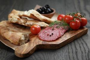 antipasti med salami, oliver, tomater och bröd foto