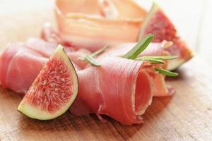 kanapéer med jamon och fikon på träplatta foto