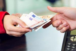 kvinna kund betalar med pengar. händer detalj. foto