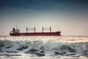 solnedgång vid havet med seglande lastfartyg foto