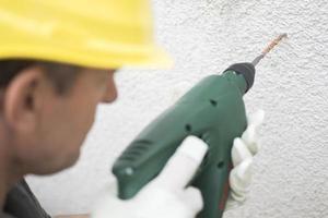 byggnadsarbetare som använder elektrisk borr på betongväggen foto