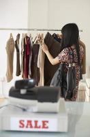 kvinna shopping kläder i försäljning foto