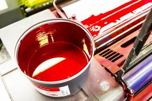 tryckmaskin och färgkanna foto