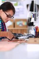 modedesigner som klipper textil bredvid en symaskin foto