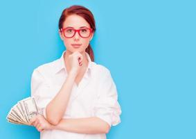 porträtt av rödhårig kvinna i röda glasögon med pengar