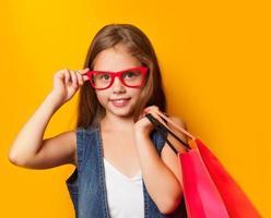 flicka i röda glasögon med shoppingväska foto