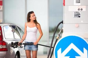 kvinna tankar sin bil i en bensinstation foto