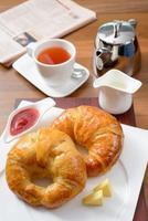 frukost med croissant, sylt och engelsk te foto