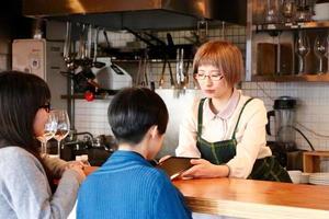 ung caféägare som använder den digitala surfplattan foto