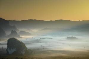 vackert landskap och dimma som täcker på fältet på morgonen. foto