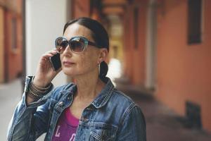 ringande kvinna med solglasögon på gatorna i Bologna, Italien. foto