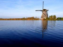 traditionell holländsk väderkvarn nära kanalen. nederländerna foto