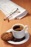 kaffe med kaka och tidning foto