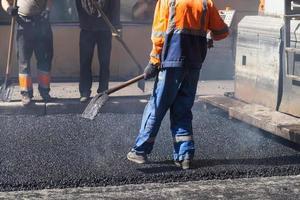 pågående asfalt, arbetare med spade foto