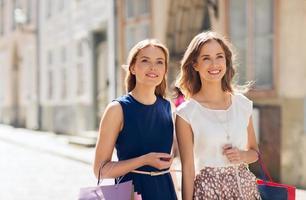 glada kvinnor med påsar som går i staden foto