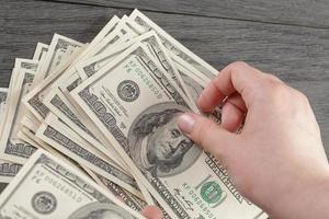 unga kvinnliga händer räknar dollarsedlar på träbord foto