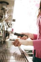 barista som gör kaffe med en kaffemaskin foto