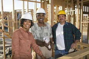 två män och kvinnor med ritningar på byggarbetsplatsen, porträtt foto