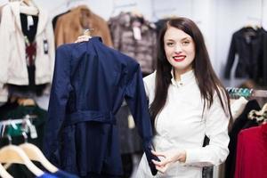 kvinna som väljer jacka på boutique foto