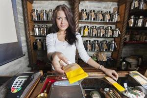 säker självförsäljare som lämnar papperspåse fylld med te i butiken foto