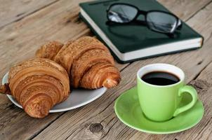gröna kopp espressokaffe med croissanter foto