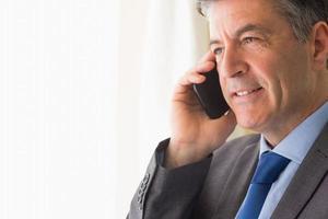 tankeväckande man som ringer någon med sin mobiltelefon foto