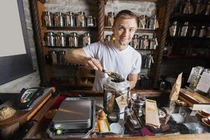porträtt av säljaren skopa te från containern i butiken foto
