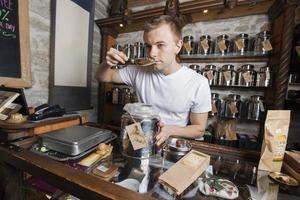 försäljare som luktar te i butiken foto