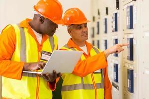 två elektriker som kontrollerar industriell kontrollbox foto