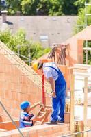 arbetare som kontrollerar väggar på byggarbetsplatsen foto