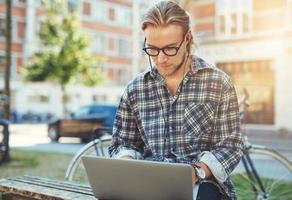 koncentrerad ung man med sin bärbara dator foto