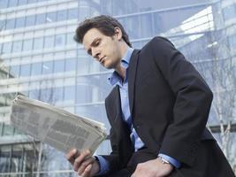 affärsman som läser tidningen utomhus foto
