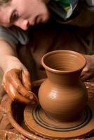 händerna på en keramiker som skapar en lerkrukan