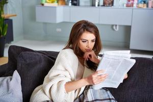 ung glad kvinna läser tidningen foto