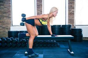 kvinna träning med hantel på bänken foto