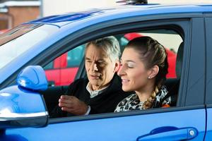 ung kvinna tar instruktioner från sin körinstruktör foto