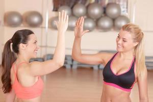 två flickvänner som ger high five i gymmet foto